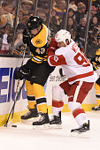 Matt Bartkowski of the Boston Bruins fights for the puck against Stephen Weiss of the Detroit Red Wings at the TD Garden on December 29 2014 in...