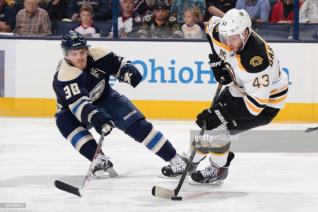<a gi-track='captionPersonalityLinkClicked' href=/galleries/search?phrase=Matt+Bartkowski&family=editorial&specificpeople=7203779 ng-click='$event.stopPropagation()'>Matt Bartkowski</a> #43 of the Boston Bruins skates the puck around the out stretched stick of <a gi-track='captionPersonalityLinkClicked' href=/galleries/search?phrase=Boone+Jenner&family=editorial&specificpeople=6480665 ng-click='$event.stopPropagation()'>Boone Jenner</a> #38 of the Columbus Blue Jackets during the third period on October 12, 2013 at Nationwide Arena in Columbus, Ohio. Boston defeated Columbus 3-1.