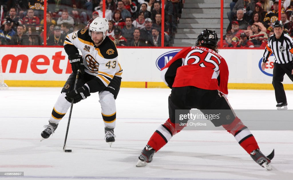 <a gi-track='captionPersonalityLinkClicked' href=/galleries/search?phrase=Matt+Bartkowski&family=editorial&specificpeople=7203779 ng-click='$event.stopPropagation()'>Matt Bartkowski</a> #43 of the Boston Bruins stickhandles the puck against Erik Karlsson #65 of the Ottawa Senators during an NHL game at Canadian Tire Centre on December 28, 2013 in Ottawa, Ontario, Canada.