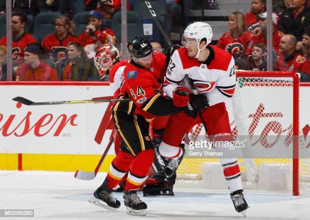 Matt Bartkowski of the Calgary Flames battles against Brett Pesce of the Carolina Hurricanes at Scotiabank Saddledome on October 19 2017 in Calgary...