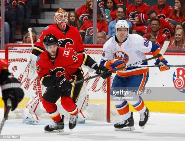 Matt Bartkowski of the Calgary Flames battles against Nikolay Kulemin of the New York Islanders at Scotiabank Saddledome on March 5 2017 in Calgary...