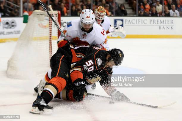 Matt Bartkowski of the Calgary Flames battles Antoine Vermette of the Anaheim Ducks for a loose puck during the first period of Game Two of the...