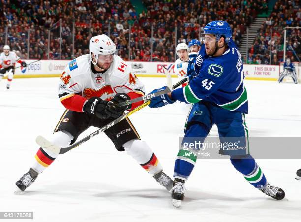 Matt Bartkowski of the Calgary Flames checks Michael Chaput of the Vancouver Canucks during their NHL game at Rogers Arena February 18 2017 in...