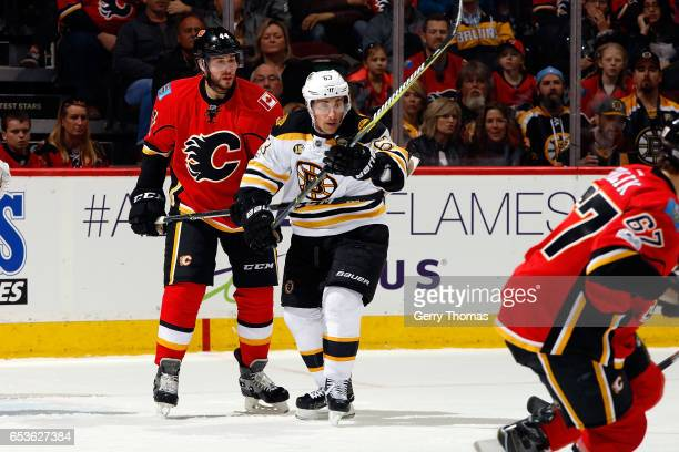 Matt Bartkowski of the Calgary Flames skates against Brad Marchand of the Boston Bruins during an NHL game on March 15 2017 at the Scotiabank...