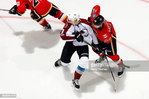 Matt Bartkowski of the Calgary Flames skates against Joe Colborne of the Colorado Avalanche during an NHL game on March 27 2017 at the Scotiabank...