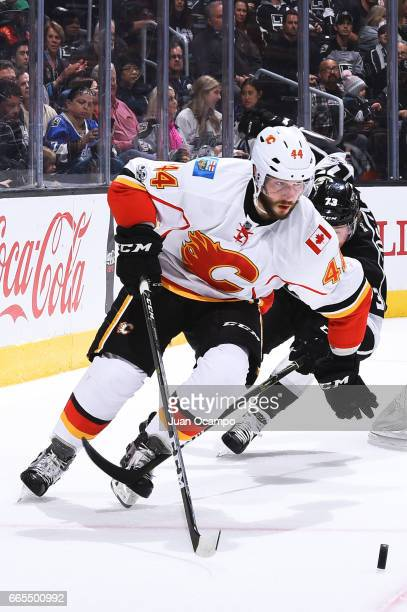 Matt Bartkowski of the Calgary Flames skates with the puck with pressure from Tyler Toffoli of the Los Angeles Kings during the game on April 6 2017...
