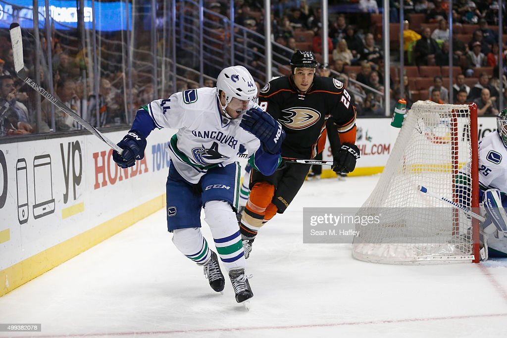 Matt Bartkowski #44 of the Vancouver Canucks grimaces as Chris Stewart #29 of the Anaheim Ducks follows the play during the third period of a game at Honda Center on November 30, 2015 in Anaheim, California.