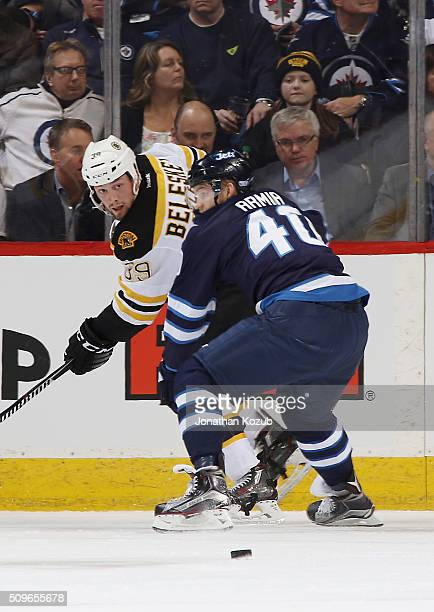 Matt Beleskey of the Boston Bruins and Joel Armia of the Winnipeg Jets battle along the boards as the puck squirts loose during second period action...