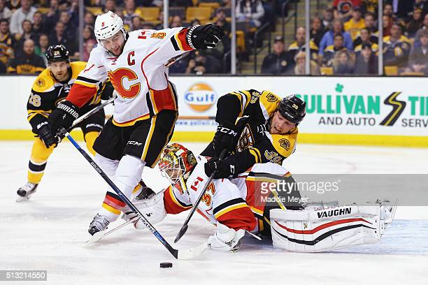Matt Beleskey of the Boston Bruins takes a shot over Joni Ortio of the Calgary Flames with pressure from Mark Giordano during the first period at TD...