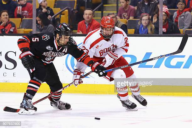 Matt Benning of the Northeastern Huskies and Jakob Forsbacka Karlsson of the Boston University Terriers battle for the puck during the third period...
