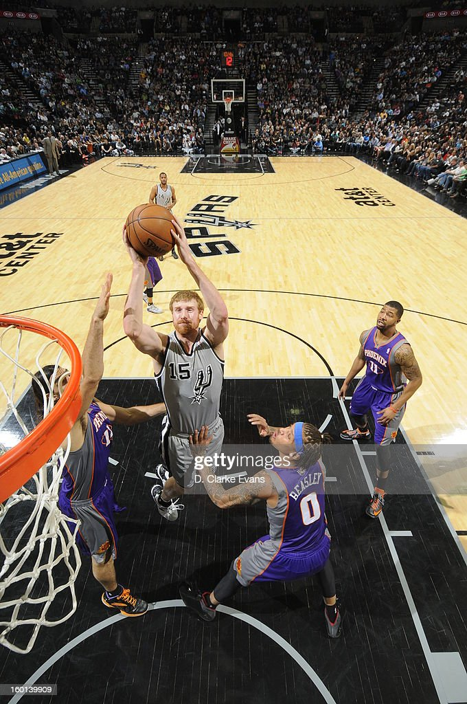 Matt Bonner #15 of the San Antonio Spurs shoots against Michael Beasley #0 of the Phoenix Suns on January 26, 2013 at the AT&T Center in San Antonio, Texas.