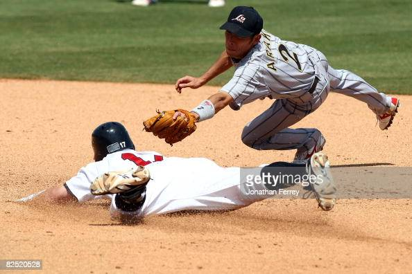 Matt Brown of the UNited States slides safely into second base for a double ahead of the tag attempt by Masahiro Araki of Japan in the bottom of the...