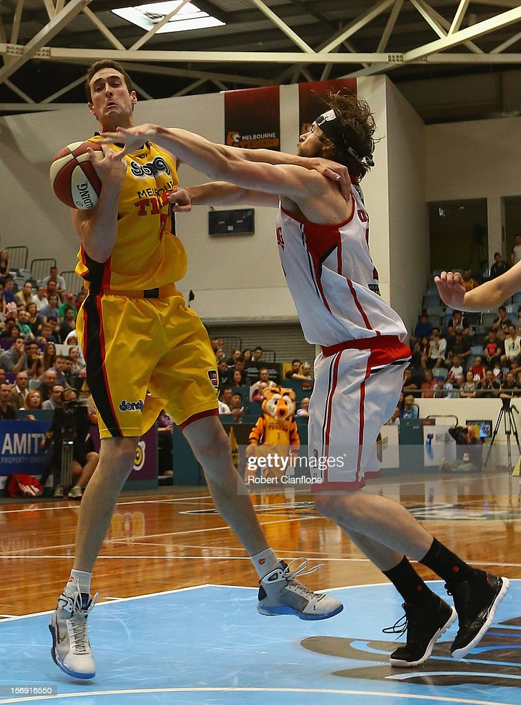 Matt Burston of the Tigers and Larry Davidson of the Hawks challenge each other for the ball during the round eight NBL match between the Melbourne Tigers and the Wollongong Hawks at State Netball Hockey Centre on November 25, 2012 in Melbourne, Australia.