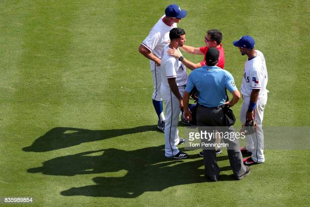 Matt Bush of the Texas Rangers leaves the game after colliding with Joey Gallo of the Texas Rangers while fielding the ball against the Chicago White...