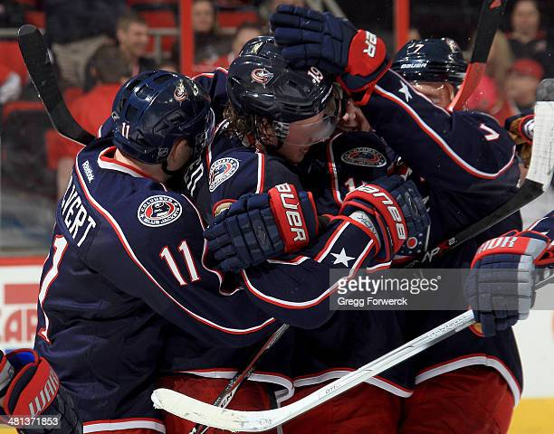 Matt Calvert and Jack Johnson of the Columbus Blue Jackets surround Ryan Johansen following his overtime gamewinning goal against the Carolina...