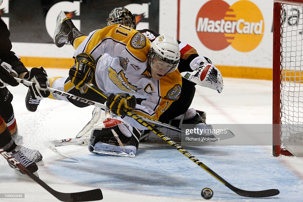 Matt Calvert #11 of the Brandon Wheat Kings trips over Martin Jones #31 of the Calgary Hitmen during the 2010 Mastercard Memorial Cup Tournament at the Keystone Centre on May 19, 2010 in Brandon, Manitoba, Canada.