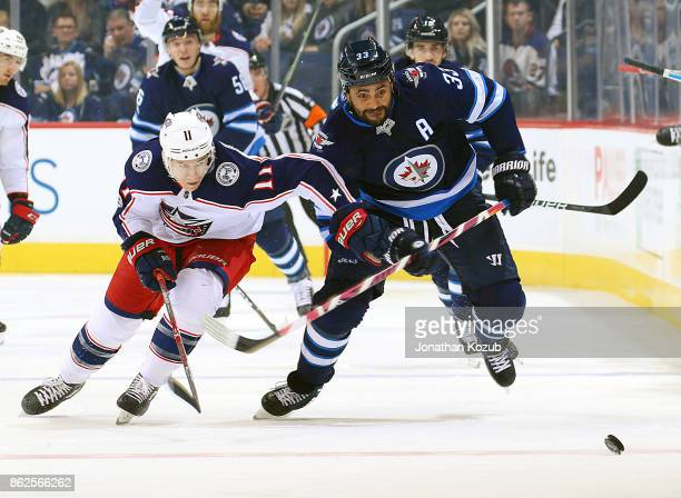 Matt Calvert of the Columbus Blue Jackets and Dustin Byfuglien of the Winnipeg Jets chase the loose puck down the ice during first period action at...