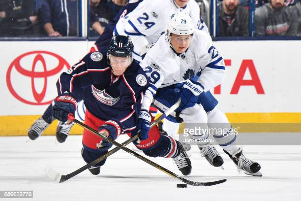 Matt Calvert of the Columbus Blue Jackets and William Nylander of the Toronto Maple Leafs battle for a loose puck during the first period of a game...