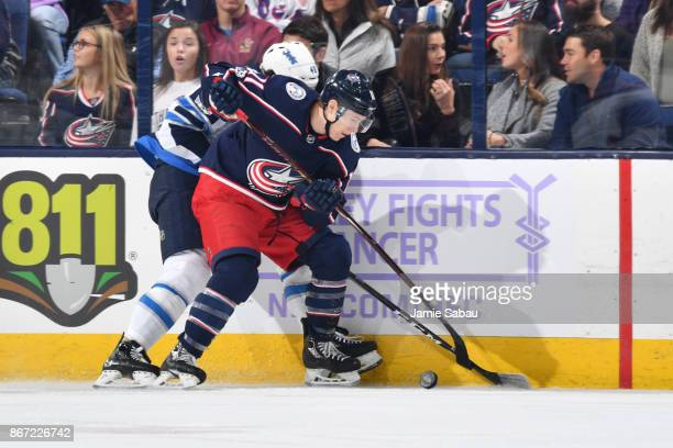 Matt Calvert of the Columbus Blue Jackets battles for the puck with Brendan Lemieux of the Winnipeg Jets during the first period of a game on October...