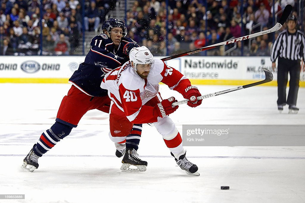 Matt Calvert #11 of the Columbus Blue Jackets checks Henrik Zetterberg #40 of the Detroit Redwings while chasing after the puck during the first period on January 21, 2013 at Nationwide Arena in Columbus, Ohio.