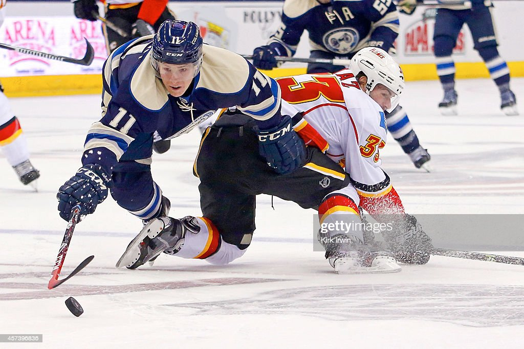 Matt Calvert of the Columbus Blue Jackets dives over Rapheal Diaz of the Calgary Flames in an effort to gain control of the puck during the second...