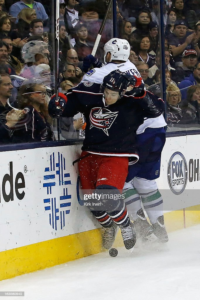 Matt Calvert #11 of the Columbus Blue Jackets is checked by Cam Barker #18 of the Vancouver Canucks while chasing after a loose puck during the second period on March 12, 2013 at Nationwide Arena in Columbus, Ohio.