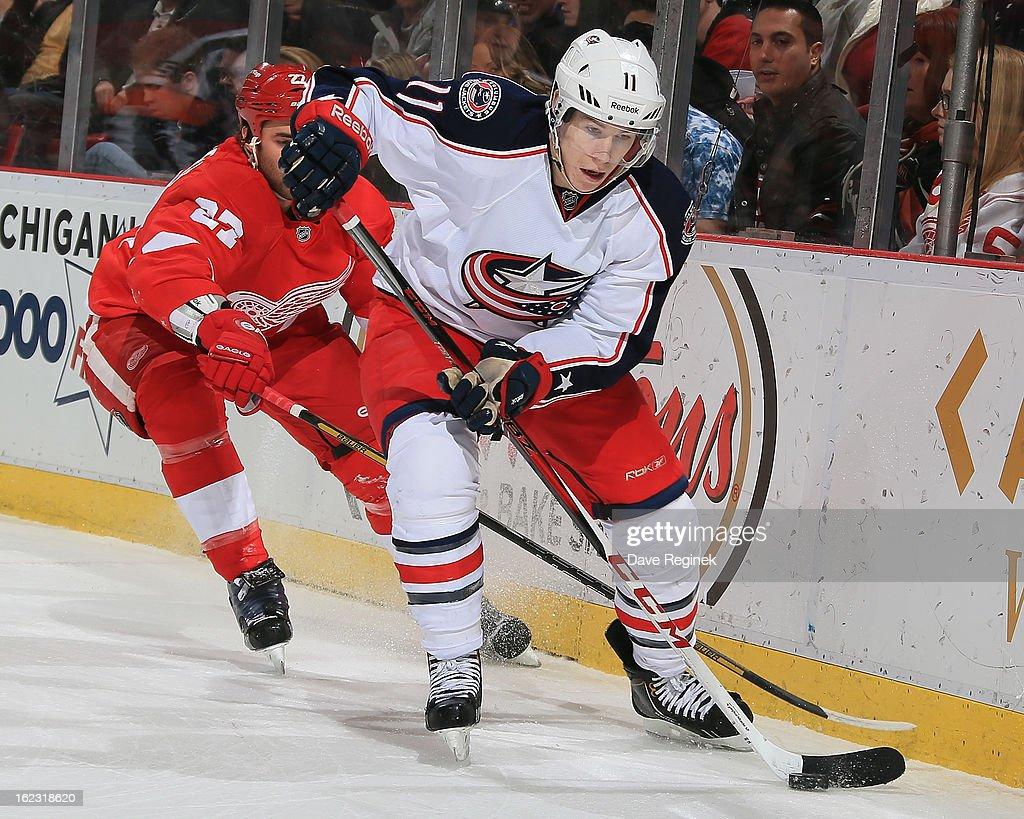Matt Calvert #11 of the Columbus Blue Jackets protects the puck from Kyle Quincey #27 of the Detroit Red Wings during a NHL game at Joe Louis Arena on February 21, 2013 in Detroit, Michigan. Columbus won 3-2