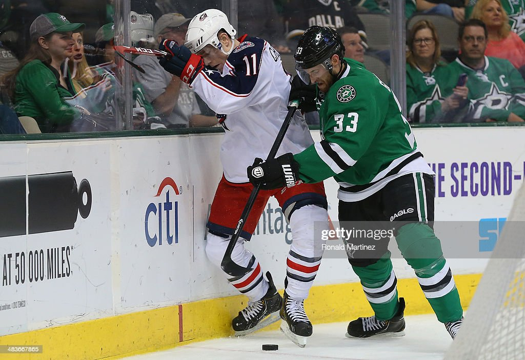 Matt Calvert #11 of the Columbus Blue Jackets skates the puck against Alex Goligoski #33 of the Dallas Stars in the second period at American Airlines Center on April 9, 2014 in Dallas, Texas.