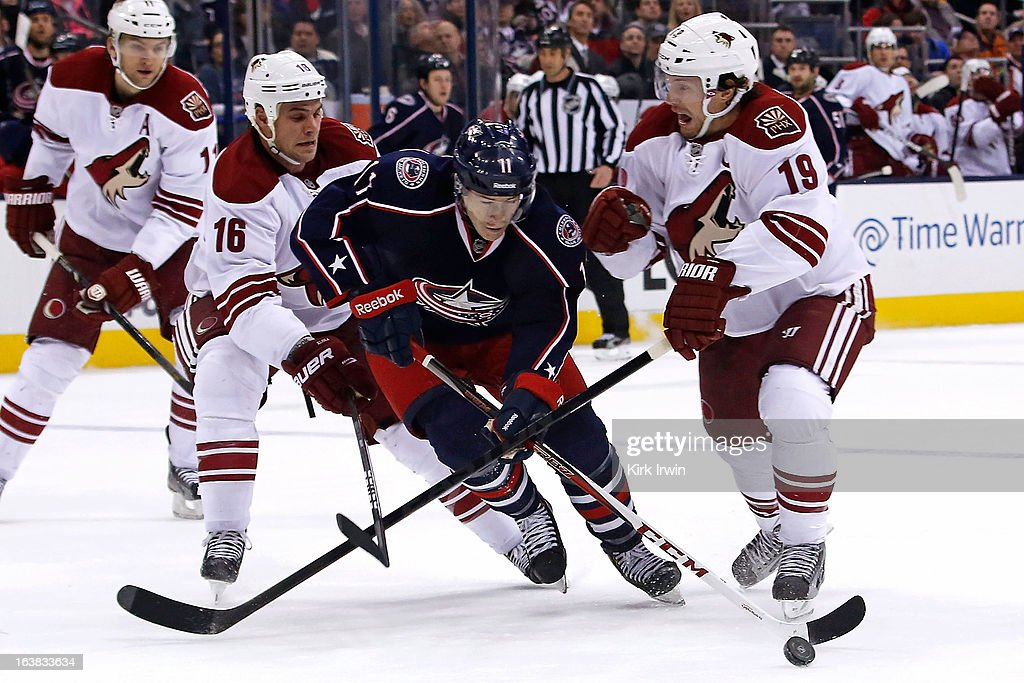 Matt Calvert #11 of the Columbus Blue Jackets slips through Rostislav Klesla #16 of the Phoenix Coyotes and Shane Doan #19 of the Phoenix Coyotes while chasing after a loose puck during the second period on March 16, 2013 at Nationwide Arena in Columbus, Ohio.