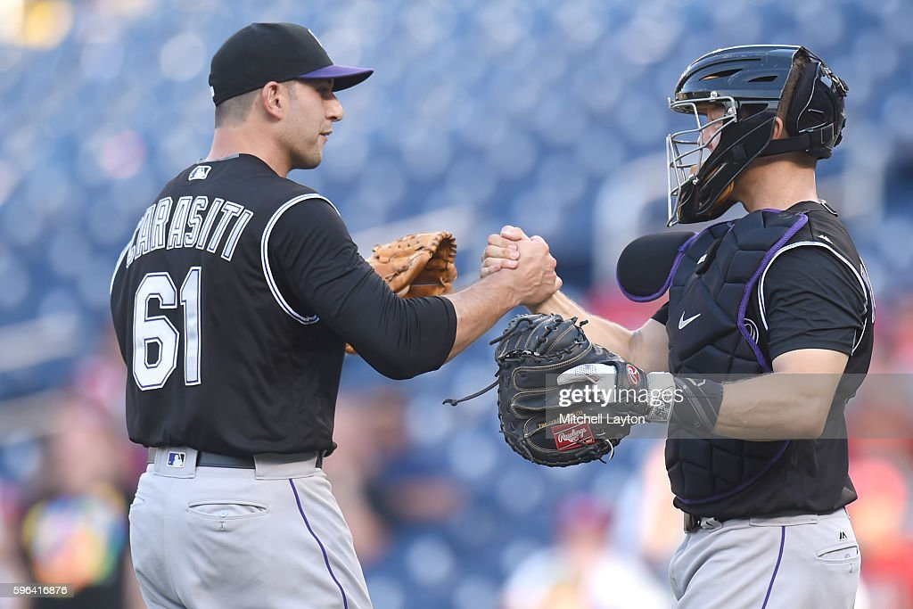 Matt Carasiti #61 and Nick Hundley #4 of the Colorado Rockies celebrate a win after a baseball game against the Washington Nationals at Nationals Park on August 27, 2016 in Washington, DC.