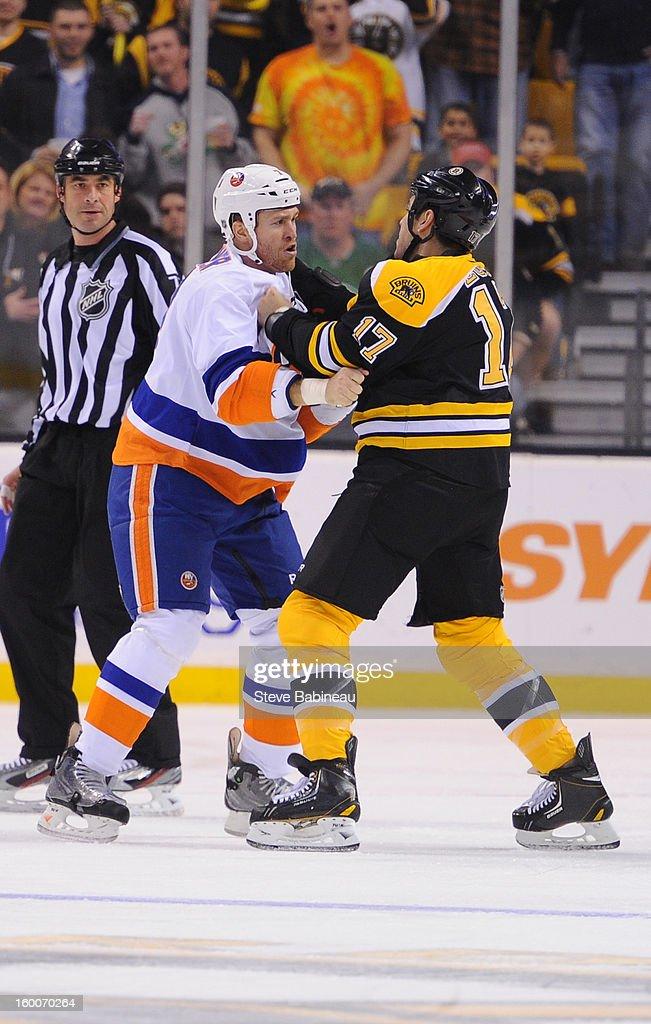 Matt Carkner #7 of the New York Islanders fights against Milan Lucic #17 of the Boston Bruins at the TD Garden on January 25, 2013 in Boston, Massachusetts.