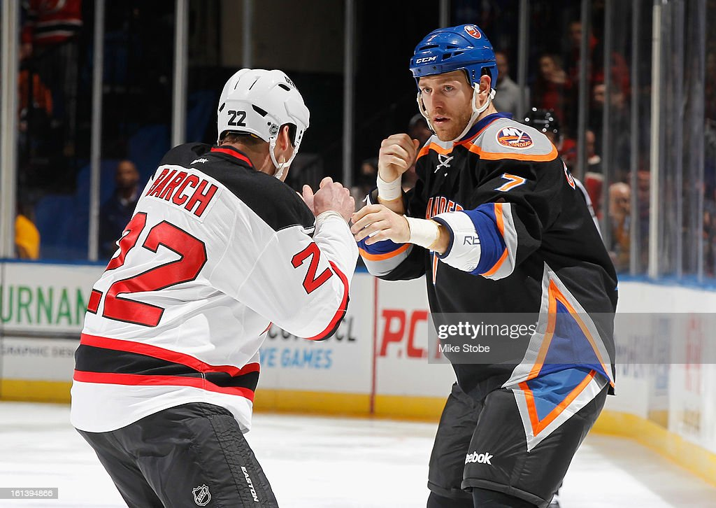 Matt Carkner #7 of the New York Islanders gets tangled up with Krys Barch #22 of the New Jersey Devils at Nassau Veterans Memorial Coliseum on Febuary 3, 2013 in Uniondale, New York.