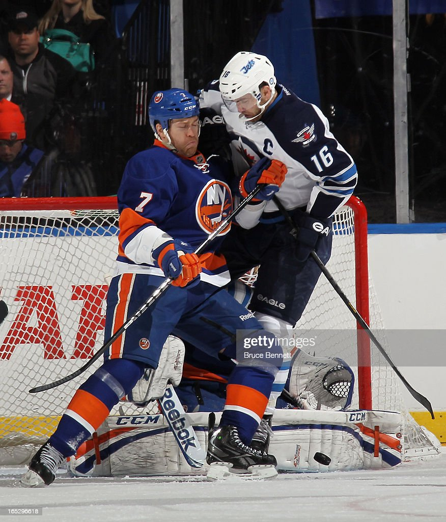 Matt Carkner #7 of the New York Islanders moves Andrew Ladd #16 of the Winnipeg Jets out of the crease at the Nassau Veterans Memorial Coliseum on April 2, 2013 in Uniondale, New York.