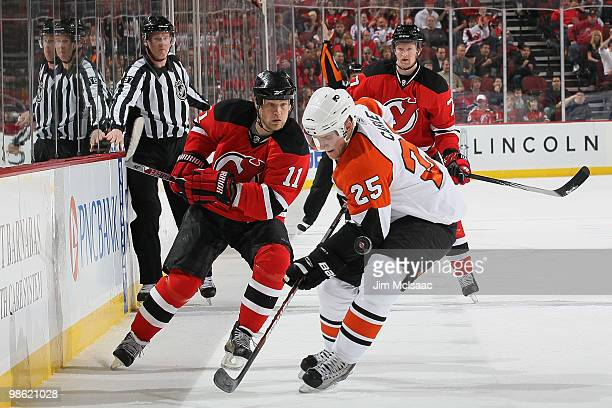 Matt Carle of the Philadelphia Flyers fights for the puck against Dean McAmmond of the New Jersey Devils in Game 5 of the Eastern Conference...