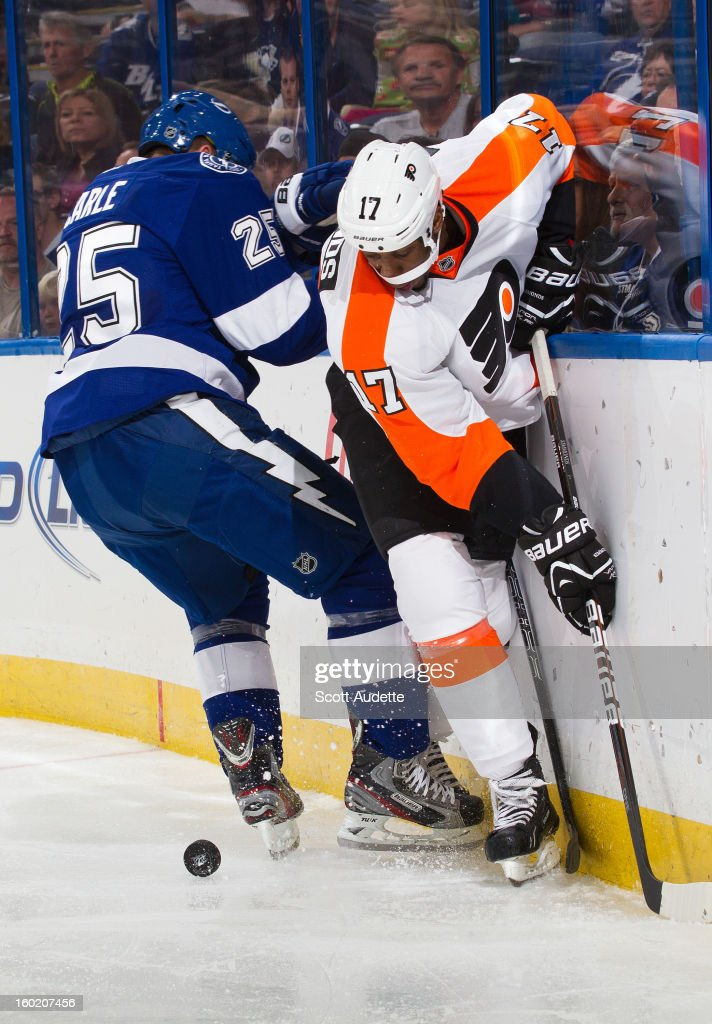 Matt Carle #25 of the Tampa Bay Lightning and Wayne Simmonds #17 of the Philadelphia Flyers battle for the puck during the second period of an NHL game at the Tampa Bay Times Forum on January 27, 2013 in Tampa, Florida.
