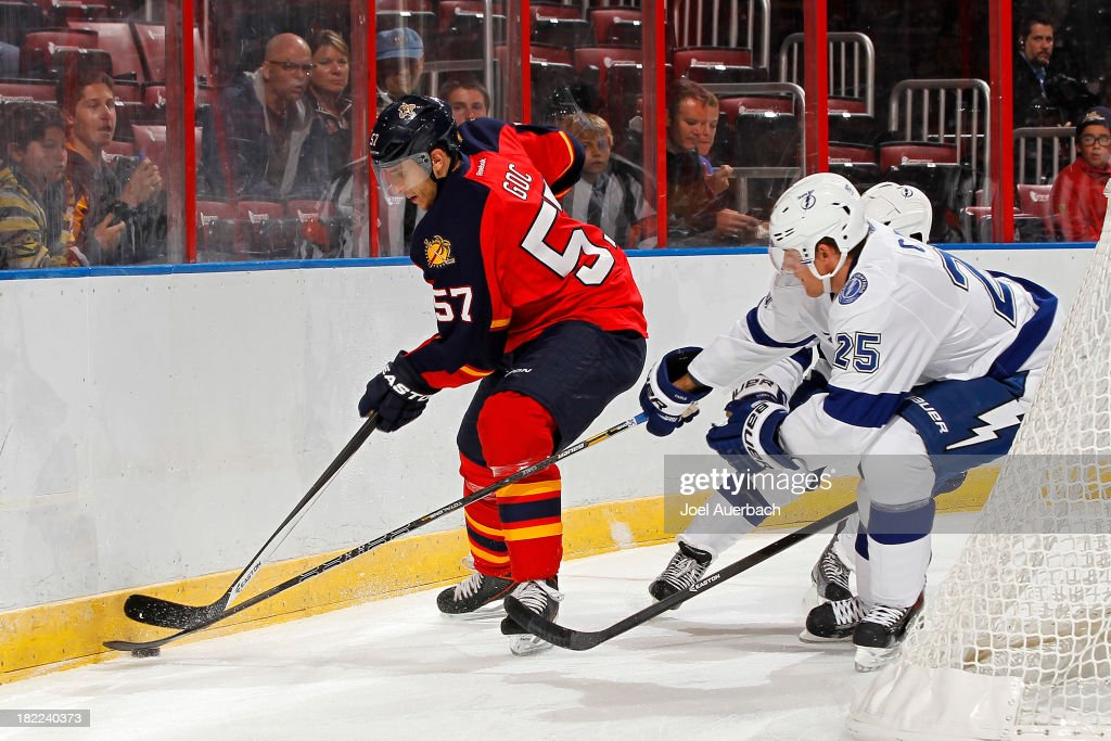 <a gi-track='captionPersonalityLinkClicked' href=/galleries/search?phrase=Matt+Carle&family=editorial&specificpeople=582495 ng-click='$event.stopPropagation()'>Matt Carle</a> #25 of the Tampa Bay Lightning attempts to check <a gi-track='captionPersonalityLinkClicked' href=/galleries/search?phrase=Marcel+Goc&family=editorial&specificpeople=541626 ng-click='$event.stopPropagation()'>Marcel Goc</a> #57 of the Florida Panthers off the puck behind the net at the BB&T Center on September 28, 2013 in Sunrise, Florida.