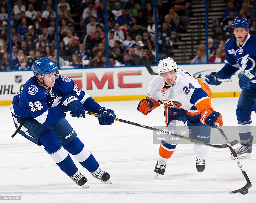 <a gi-track='captionPersonalityLinkClicked' href=/galleries/search?phrase=Matt+Carle&family=editorial&specificpeople=582495 ng-click='$event.stopPropagation()'>Matt Carle</a> #25 of the Tampa Bay Lightning attempts to gain control of the puck from <a gi-track='captionPersonalityLinkClicked' href=/galleries/search?phrase=Brad+Boyes&family=editorial&specificpeople=275014 ng-click='$event.stopPropagation()'>Brad Boyes</a> #24 of the New York Islanders during the second period of the game at the Tampa Bay Times Forum on March 14, 2013 in Tampa, Florida.