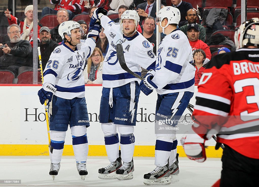 Matt Carle #25 of the Tampa Bay Lightning celebrates his third period goal against Martin Brodeur #30 of the New Jersey Devils with teammates Steven Stamkos #91 and Martin St. Louis #26 of the Tampa Bay Lightning at the Prudential Center on February 7, 2013 in Newark, New Jersey.