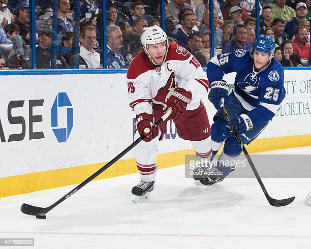 Matt Carle of the Tampa Bay Lightning chases Shane Doan of the Phoenix Coyotes during the second period at the Tampa Bay Times Forum on March 10 2014...