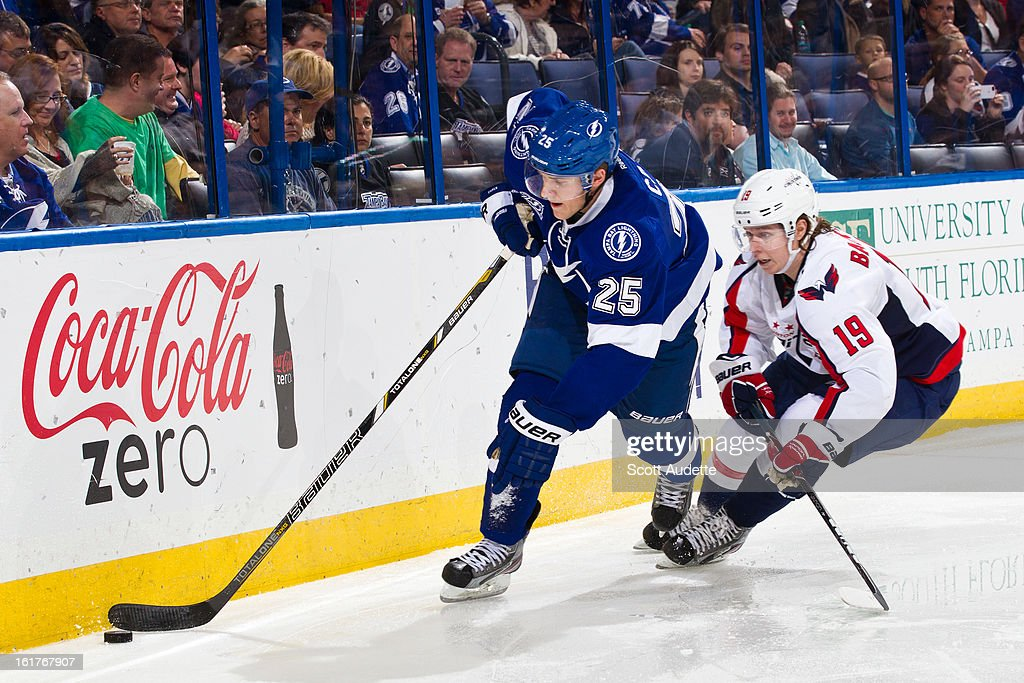 Matt Carle #25 of the Tampa Bay Lightning controls the puck ahead of Nicklas Backstrom #19 of the Washington Capitals during the second period of the game at the Tampa Bay Times Forum on February 14, 2013 in Tampa, Florida.