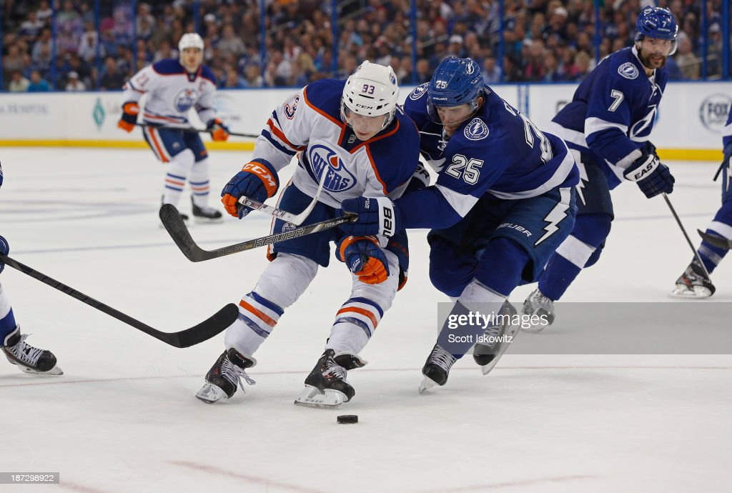 <a gi-track='captionPersonalityLinkClicked' href=/galleries/search?phrase=Matt+Carle&family=editorial&specificpeople=582495 ng-click='$event.stopPropagation()'>Matt Carle</a> #25 of the Tampa Bay Lightning defends battles for the puck against <a gi-track='captionPersonalityLinkClicked' href=/galleries/search?phrase=Steve+MacIntyre&family=editorial&specificpeople=5571785 ng-click='$event.stopPropagation()'>Steve MacIntyre</a> #33 of the Edmonton Oilers during the third period at Tampa Bay Times Forum on November 7, 2013 in Tampa, Florida.