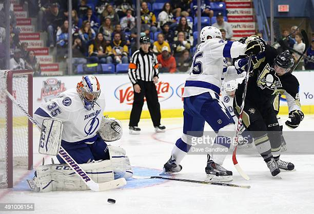 Matt Carle of the Tampa Bay Lightning defends Dominik Uher of the Pittsburgh Penguins as goaltender Kevin Poulin during the third period of the NHL...