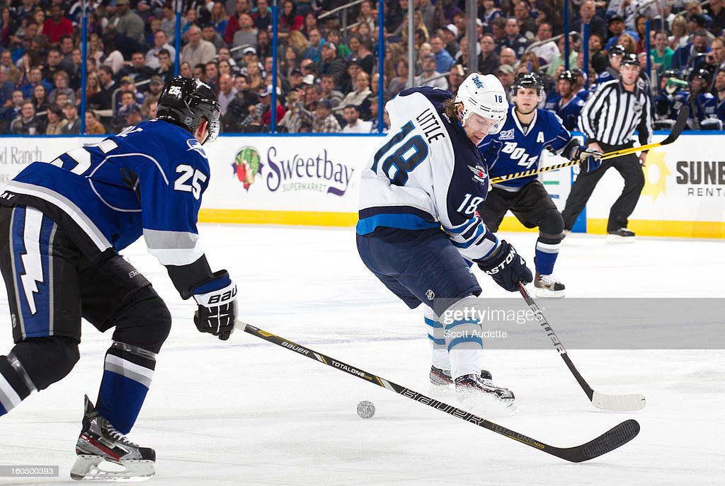 <a gi-track='captionPersonalityLinkClicked' href=/galleries/search?phrase=Matt+Carle&family=editorial&specificpeople=582495 ng-click='$event.stopPropagation()'>Matt Carle</a> #25 of the Tampa Bay Lightning skates behind <a gi-track='captionPersonalityLinkClicked' href=/galleries/search?phrase=Bryan+Little&family=editorial&specificpeople=540533 ng-click='$event.stopPropagation()'>Bryan Little</a> #18 of the Winnipeg Jets as he receives a pass during the second period of the game at the Tampa Bay Times Forum on February 1, 2013 in Tampa, Florida.