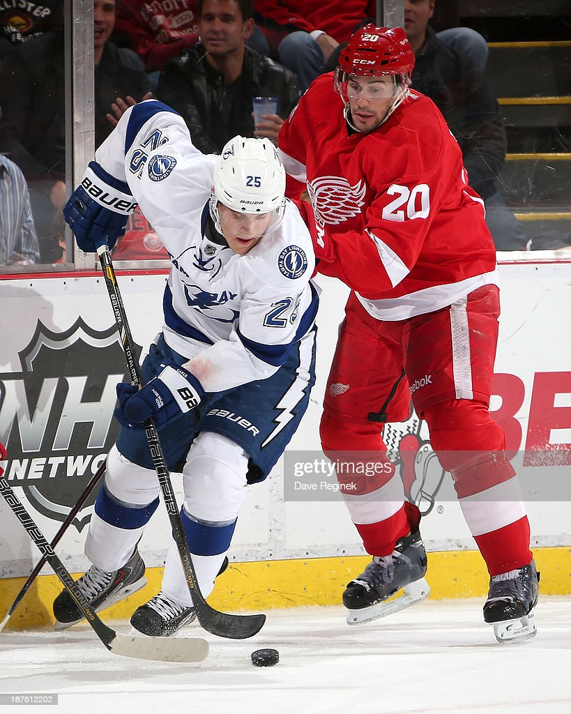 <a gi-track='captionPersonalityLinkClicked' href=/galleries/search?phrase=Matt+Carle&family=editorial&specificpeople=582495 ng-click='$event.stopPropagation()'>Matt Carle</a> #25 of the Tampa Bay Lightning skates out of the corner past Drew Miller #20 of the Detroit Red Wings during an NHL game at Joe Louis Arena on November 9, 2013 in Detroit, Michigan. Tampa Bay defeated Detroit 3-2 in OT