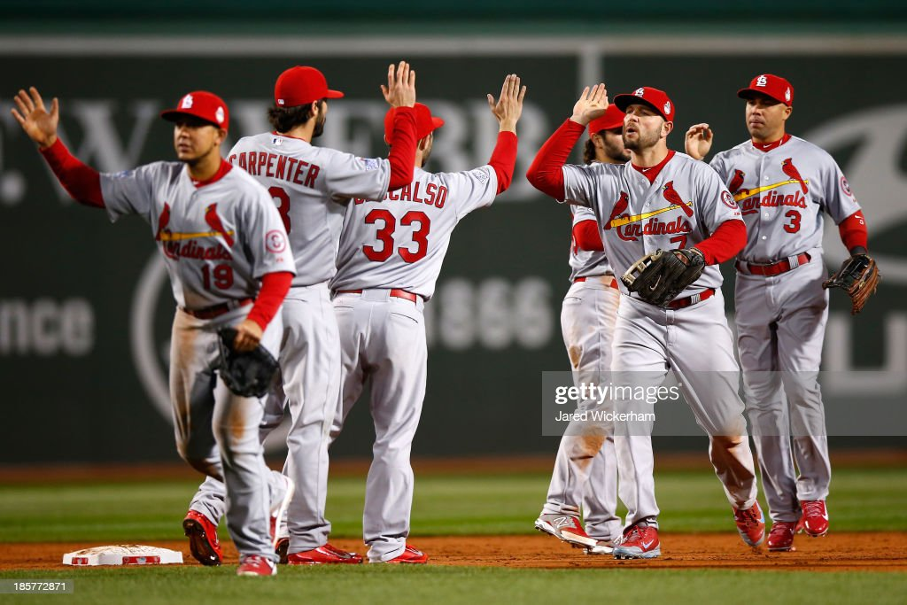 Matt Carpenter #13 and <a gi-track='captionPersonalityLinkClicked' href=/galleries/search?phrase=Matt+Holliday&family=editorial&specificpeople=207017 ng-click='$event.stopPropagation()'>Matt Holliday</a> #7 of the St. Louis Cardinals celebrate after defeating the Boston Red Sox 4-2 in Game Two of the 2013 World Series at Fenway Park on October 24, 2013 in Boston, Massachusetts.