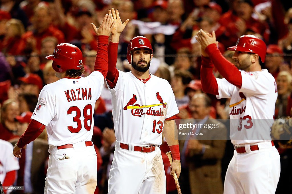 Matt Carpenter #13 congratulates <a gi-track='captionPersonalityLinkClicked' href=/galleries/search?phrase=Pete+Kozma&family=editorial&specificpeople=6800748 ng-click='$event.stopPropagation()'>Pete Kozma</a> #38 and <a gi-track='captionPersonalityLinkClicked' href=/galleries/search?phrase=Daniel+Descalso&family=editorial&specificpeople=6800752 ng-click='$event.stopPropagation()'>Daniel Descalso</a> #33 of the St. Louis Cardinals after both score on a RBI double by Jon Jay #19 in the sixth inning against the San Francisco Giants in Game Four of the National League Championship Series at Busch Stadium on October 18, 2012 in St Louis, Missouri.