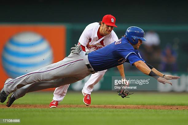 Matt Carpenter of the St Louis Cardinals attempts to double up Mitch Moreland of the Texas Rangers at second base in the second inning at Busch...