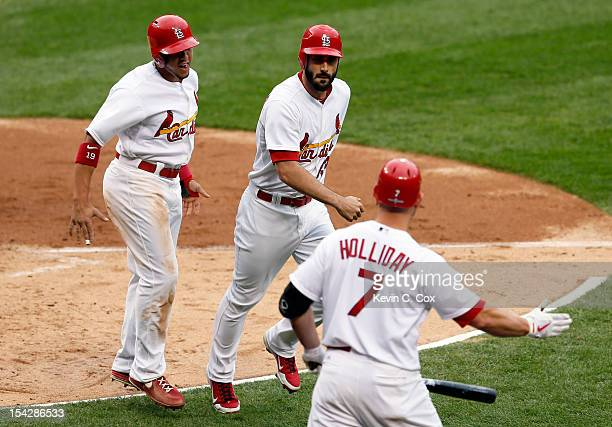 Matt Carpenter of the St Louis Cardinals celebrates after hitting a tworun home run with teammates Jon Jay and Matt Holliday in the third inning...