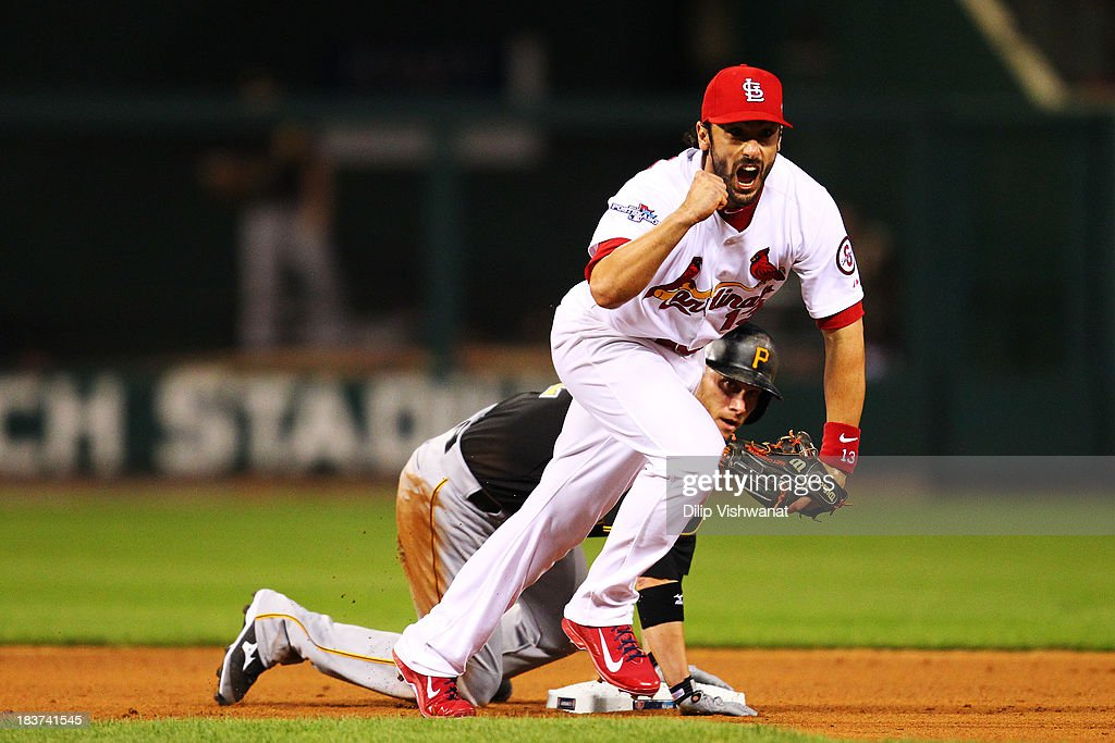 Matt Carpenter #13 of the St. Louis Cardinals celebrates making a double play on a ball hit by Starling Marte #6 as Clint Barmes #12 of the Pittsburgh Pirates reacts in the sixth inning of Game Five of the National League Division Series at Busch Stadium on October 9, 2013 in St Louis, Missouri.