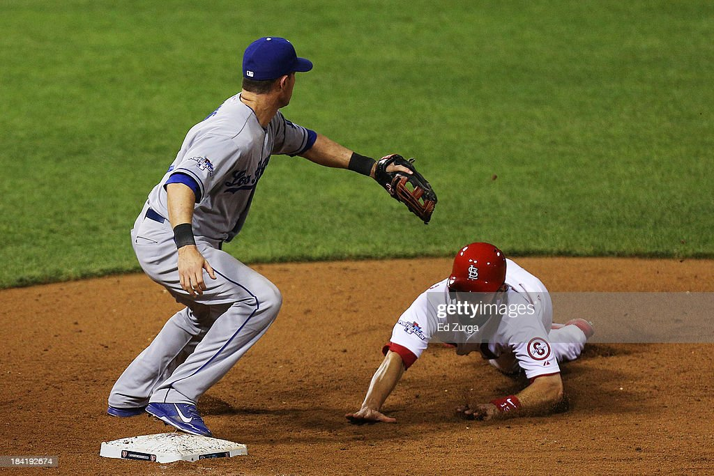 Matt Carpenter of the St Louis Cardinals dives back to first base against Michael Young of the Los Angeles Dodgers in the 11th inning during Game One...